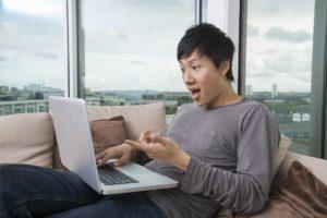 homme surpris devant son notebook