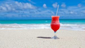 verre de cocktail posé sur une plage paradisiaque
