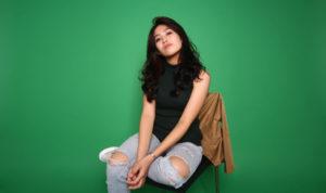 femme assise devant un fond vert